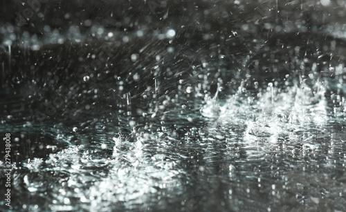 Foto auf Leinwand Wasserfalle Heavy rain falling down on ground against dark background