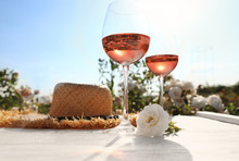 Glasses Of Rose Wine, Straw Hat And Beautiful Flower On White Wooden Table Outdoors. Space For Text