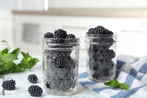 Fotografija  Glass jars of tasty ripe blackberries on marble table