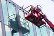 canvas print picture - Sachverständige Bauarbeiter prüfen die Glasfassade eines neuen Gebäudes und führen die Bauabnahme inkl. Qualitätskontrolle und Mängelbeseitigung mit einem Kran durch