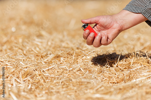 Photo Arsonist, hand holding a lighter near a haystack
