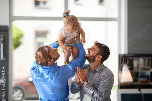 Smiling gay couple with child. Wallpaper Mural