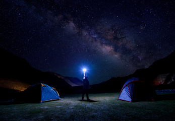 Silhouette of climber standing against the Milky Way with a flashlight in his hands. camping under the milkyway
