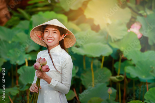Acrylic Prints Lotus flower A beautiful girl wearing a Vietnamese dress holds a large lotus flower for offering to the Buddha.