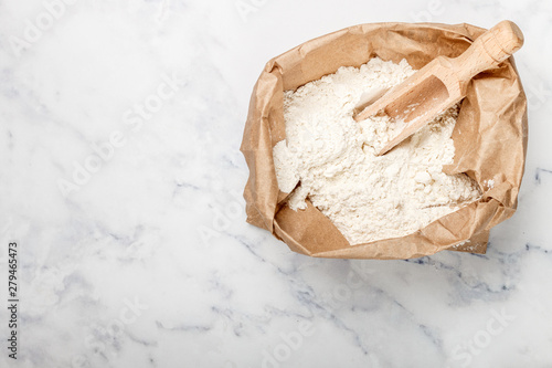 Fototapeta Wheat flour and a wooden scoop in a paper bag on a marble table