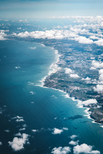 Flight Over The Coast Of Portugal Lissabon Region . Aerial View Through The Airplane Window With Clouds Water And Coastline.