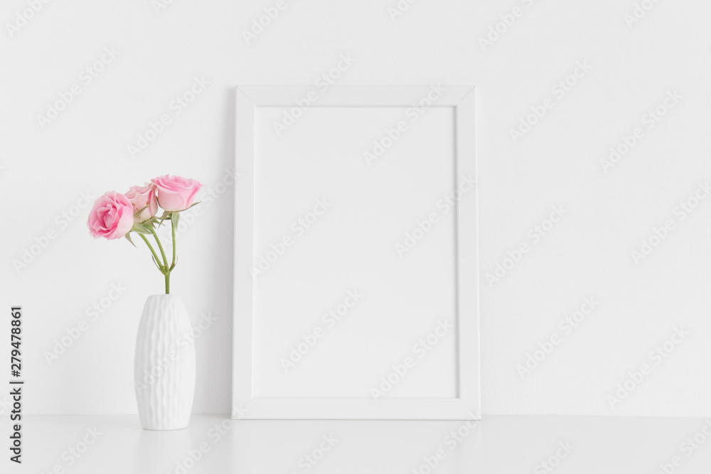 Fototapety, obrazy: White frame mockup with pink roses in a vase on a white table.Portrait orientation.