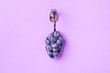 canvas print picture - curved chrome spoon with blueberry on a purple background