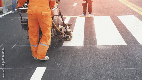 Fotografie, Obraz Road workers with thermoplastic spray road marking machine working to paint pede