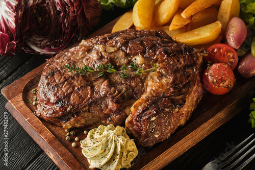 Ribeye steak with potatoes, onions and baked cherry tomatoes. Juicy steak with flavored butter - 279482679