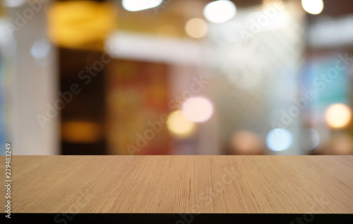Fotografering  Empty dark wooden table in front of abstract blurred bokeh background of restaurant