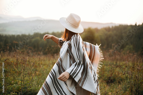 Photo Stylish boho girl walking in sunny light at atmospheric sunset in meadow