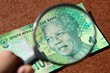 canvas print picture - South African money concept image consisting of a magnifying glass and a 10 rand note.