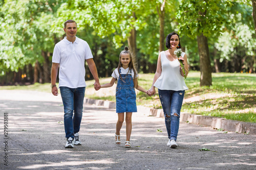 Fényképezés  Happy family, parents and the child on walk on the city park