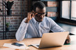 Serious african american businessman holding his eyeglasses, working with laptop in modern office