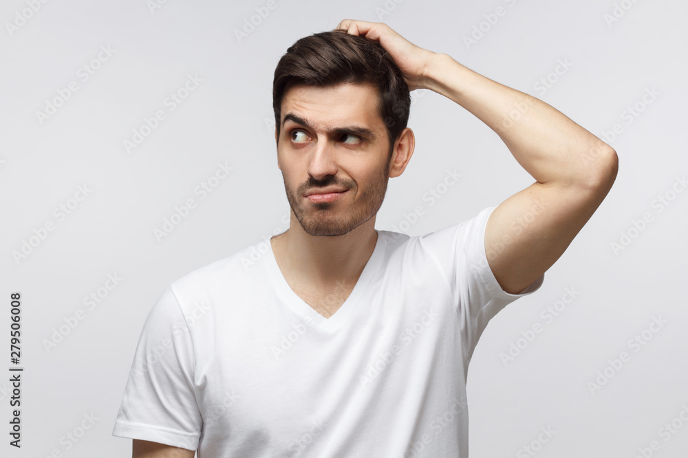 Fototapeta Young doubtful man thinking, scratching his head trying to find solution, isolated on gray background