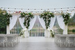 canvas print picture - Place for wedding ceremony with wedding arch decorated with palm leaves, orchid flowers and floral peacocks, bulbs garland and white chairs outdoors, copy space