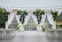 Place For Wedding Ceremony With Wedding Arch Decorated With Palm Leaves, Orchid Flowers And Floral Peacocks, Bulbs Garland And White Chairs Outdoors, Copy Space