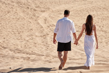 Happy Loving Couple Holding Hands  And Walking In Desert, Copy Space. Young Lovers Together On Sands In Summer