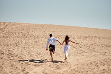 Happy Loving Couple Holding Hands  And Running In Desert, Copy Space. Young Lovers Together On Sands In Summer