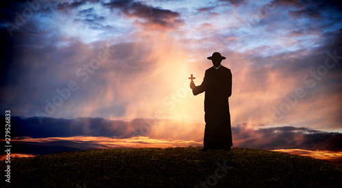 Photo pastor - priest on the hill at sunset with the cross