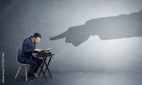 Cuadros en Lienzo  Shadow hand pointing at a small afraid worker