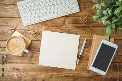 School notebook with coffee cup, smartphone and plant on wooden table. Top view from above