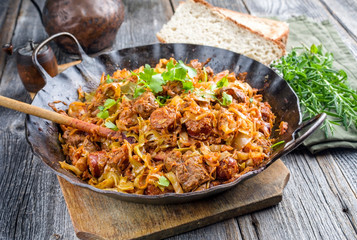 Traditional Polish kraut stew bigos with sausage, meat and mushrooms as closeup in a wrought-iron pan on an old wooden table