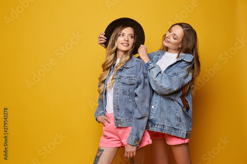 Two twins wearing jeans jackets on yellow background Canvas Print