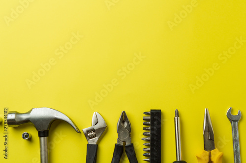 Pinturas sobre lienzo  Metal tools on a yellow background, top view, a place to sign