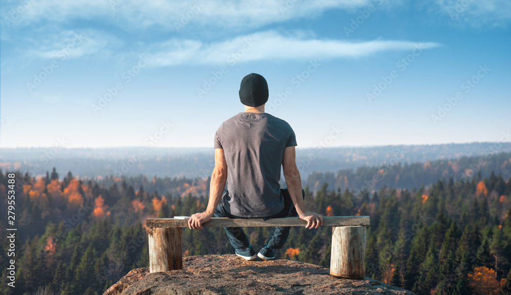Fototapety, obrazy: A man sits on a lookout point above the forest. Back view.