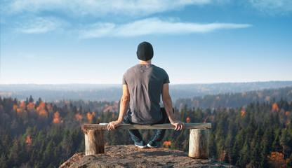 Mężczyzna siedzi na punkcie widokowym nad lasem. Widok z tyłu.