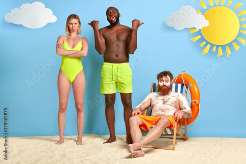 Obraz Happy dark skinned guy points at dissatisfied offended woman and funny redhead guy with sunburnt skin, protective cream on body. Three multiethnic friends spend spare time at beach. Summer rest - fototapety do salonu