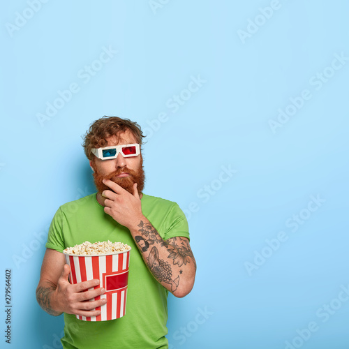 Pensive guy in 3d imax glasses, thinks over life after watching melodrama in cinema, holds chin, dressed in green clothes, holds big striped bucket with delicious popcorn Canvas Print