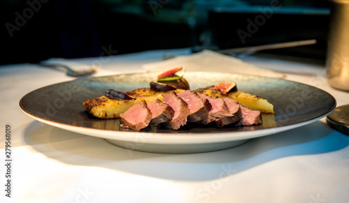 Meal on a grey plate made of meat cooked and hash browns in a high end restauran Canvas Print