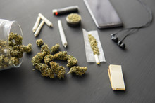 Marijuana Buds On Black Table, Grinder In Hand With Fresh Cannabis, Joint With Weed, Close Up,