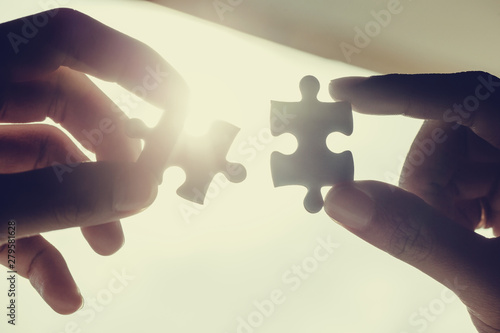 Fototapety, obrazy: Closeup hand of woman connecting jigsaw puzzle with sunlight effect, Business solutions, success and strategy concept