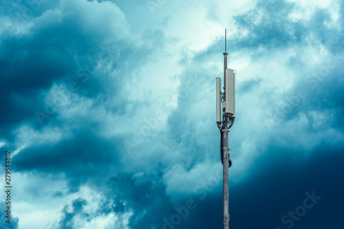 A tower with transmitters and mobile telephony antennas against the sky with clo Fototapet
