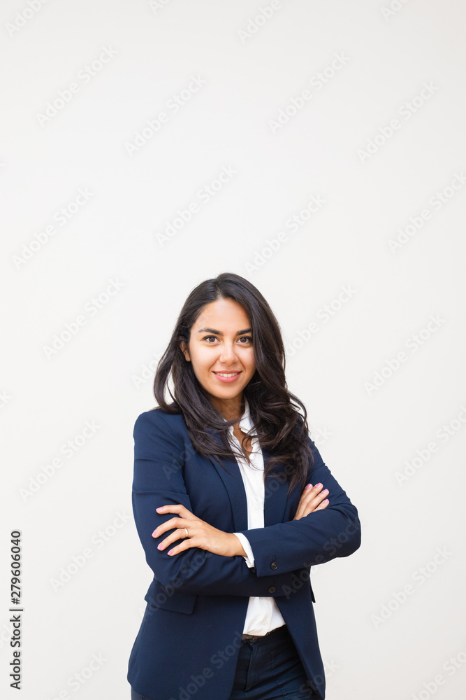 Fototapeta Confident businesswoman smiling at camera. Happy young businesswoman standing with crossed arms and looking at camera isolated on grey background. Emotion concept