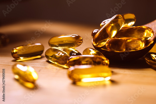 Close up the vitamin D and Omega 3 fish oil capsules supplement on wooden plate Canvas-taulu
