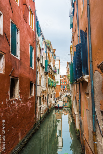 Fototapety, obrazy: Houses are reflected in a narrow channel