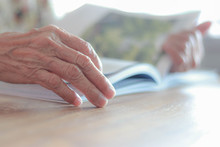 The Hands Of Elderly People Who Have Wrinkles Are To Relax And Read A Book In The Afternoon After Lunch.