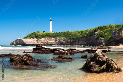 Clear water and rocks on the beach in Biarritz with the lighthouse. Basque Country of France.
