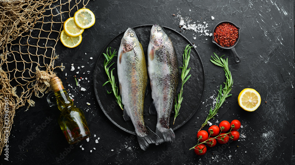 Fototapeta Raw fish trout on a plate. Top view. Free space for your text.