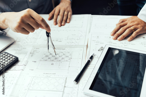 Valokuvatapetti Two engineering working together and using digital tablet looking blueprint and analysis with architectural plan on desk