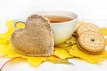 Cup Of Tea With Burlap Heart And Cookies On Autumn Leaves.