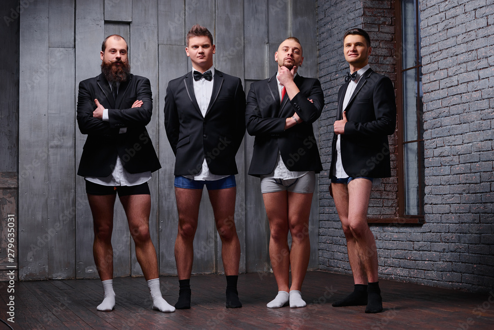 Fototapeta Confidence through friendship. A group of confident men dressed up in suits but without pants.