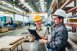 canvas print picture - Factory worker and female manager discussing about work in metal industry factory.