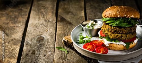 Fototapeta Vegan zucchini burger and ingredients on rustic wood background, copy space obraz