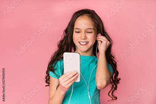 Foto  Happy schoolgirl listening music on smartphone over background